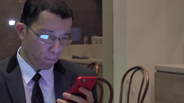 vídeos de stock e filmes b-roll de asian businessman playing smart phone at cafe - vestuário de trabalho formal