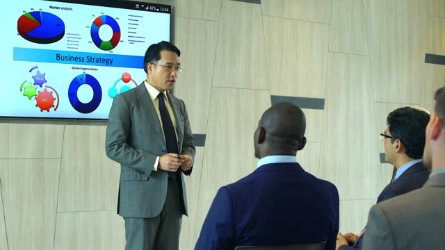 Asian businessman presenting to group of Business People during seminar or meeting about there performance.