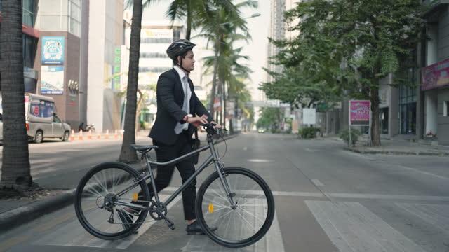 vídeos y material grabado en eventos de stock de un empresario asiático empuja una bicicleta a través de un paso de peatones en una calle de la ciudad durante un viaje diario por la mañana. - crossing