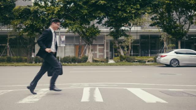 vídeos y material grabado en eventos de stock de empresario asiático corriendo al otro lado de la calle - cruzar