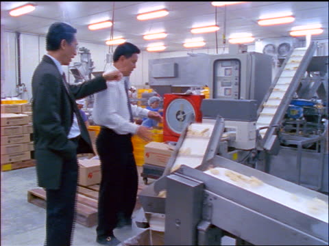 asian businessman showing conveyor belt in frozen foods factory to other businessman / indonesia - cibi surgelati video stock e b–roll