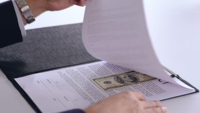 stockvideo's en b-roll-footage met aziatische zakenman teken contract wanneer zie een omkopen geld tussen contract pagina waarmee een andere zakenman voorbij aan contract aan hem. corruptie concept. - omkoping