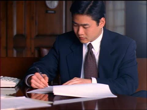 vídeos de stock e filmes b-roll de asian businessman signing contract in conference room with clock on wall - vestuário de trabalho formal