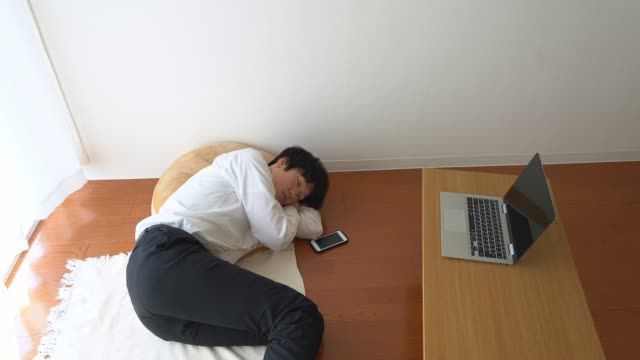 自宅からビデオ会議を開いた後、昼寝をしているアジアのビジネスマン - exhaustion点の映像素材/bロール