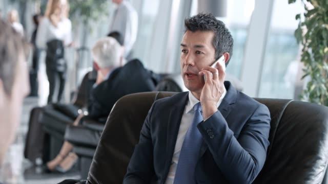 vídeos y material grabado en eventos de stock de empresario asiático hablar mientras está sentado en el salón de negocios en el aeropuerto - sillón