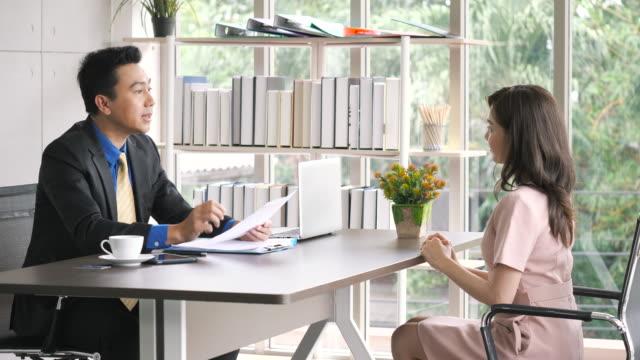 vídeos y material grabado en eventos de stock de empresario asiático hablando con la mujer solicitante en la entrevista de trabajo. - entrevista acontecimiento