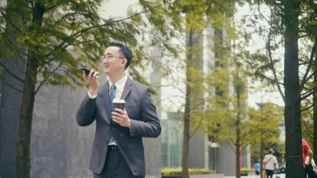 asian businessman talks over the speakerphone while drinking coffee on the street - conference phone stock videos & royalty-free footage
