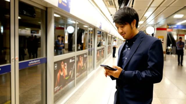 駅で電車を待っている間にスマート フォンを使用してアジア系のビジネスマンのテキスト メッセージ - 列車点の映像素材/bロール