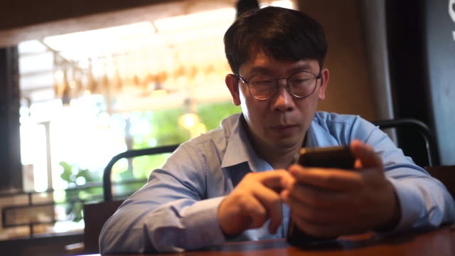 asian businessman  use smartphone and chat with friend - connection in process stock-videos und b-roll-filmmaterial