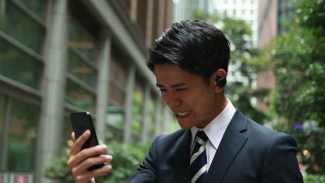 stockvideo's en b-roll-footage met aziatische zakenman die een draadloze oordopjes voor televergadering gebruikt - in ear koptelefoon