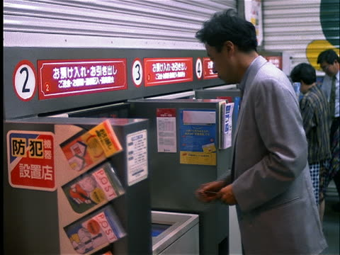 Asian businessman using ATM / Tokyo
