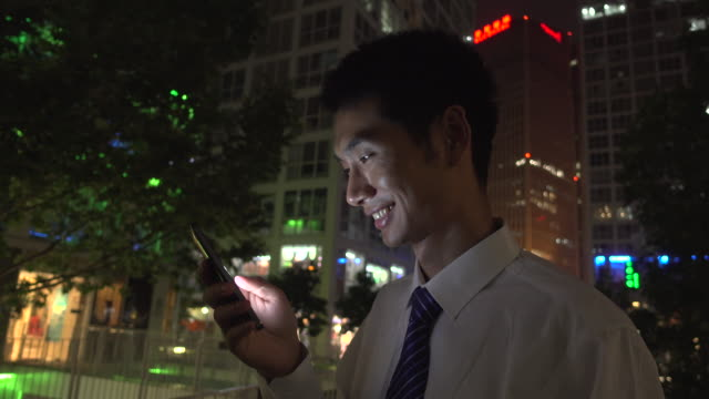 asian businessman using smart phone at city night - skjorta och slips bildbanksvideor och videomaterial från bakom kulisserna