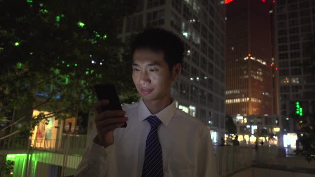 vídeos de stock e filmes b-roll de asian businessman using smart phone at city night - camisa e gravata