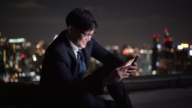 vidéos et rushes de homme d'affaires asiatique utilisant le smartphone pour travailler ou videocall son entreprise tard dans la nuit avec la ville lightbackground pour la communication de technologie chaque concept. - tenue d'affaires formelle