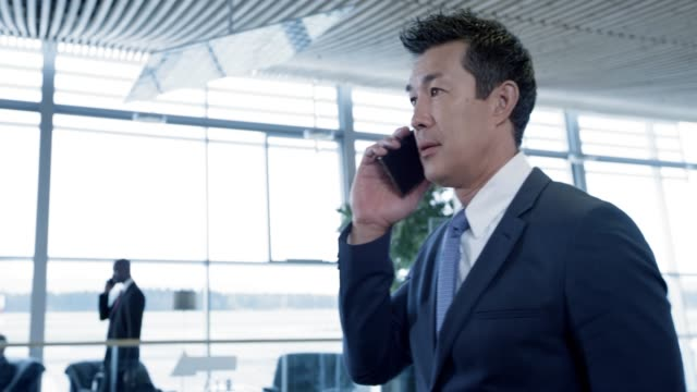 DS Asian businessman walking in airport while talking on the phone
