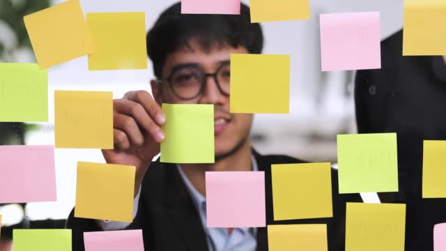 vídeos y material grabado en eventos de stock de el hombre de negocios asiático usa traje y colega lluvia de ideas con nota adhesiva en pizarra transparente en la oficina moderna. analizar y sintetizar proyecto - material