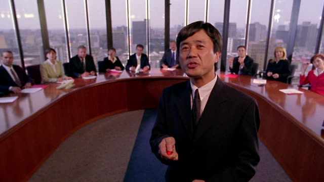 REAR VIEW Asian businessman with laser pointer giving presentation to group in conference room