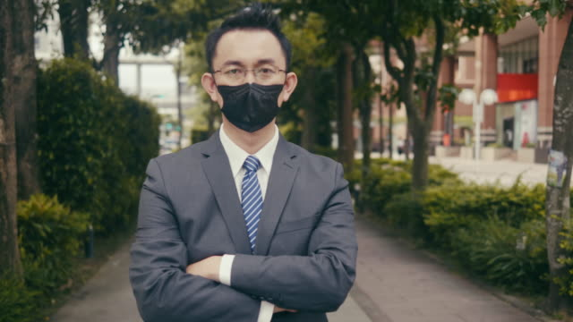 vidéos et rushes de homme d'affaires asiatique avec le masque protecteur de visage - indécision