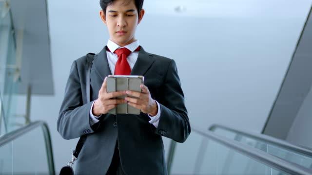 エスカレーターでタブレット コンピューターとアジア系のビジネスマン - ホワイトカラー点の映像素材/bロール