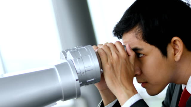 asian businessman with the binocular at the top of building