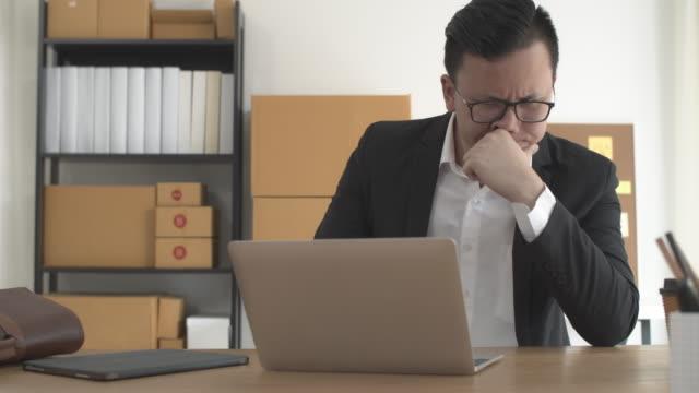 自宅でオンラインビジネスショップにラップトップで働くアジアのビジネスマン。オーナーのビジネスウーマンは、悪い経済状況でストレスや心配を感じることで起動します。 - problems点の映像素材/bロール