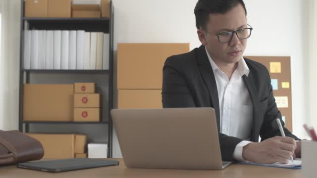自宅でオンラインビジネスショップにラップトップで働くアジアのビジネスマン。オーナーのビジネスウーマンは、悪い経済状況でストレスや心配を感じることから始めます。紙を書いて引� - 忙しい点の映像素材/bロール