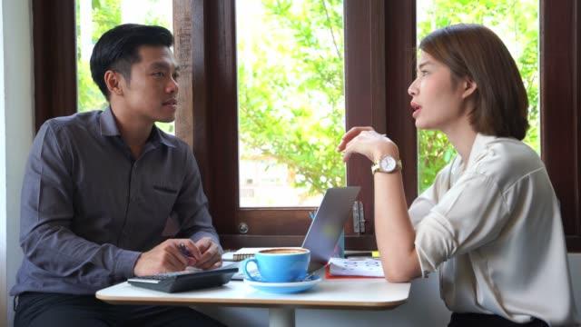 Asiatische Geschäftsleute diskutieren Vorschläge, um Ideen in Kaffeehäusern zu finden.