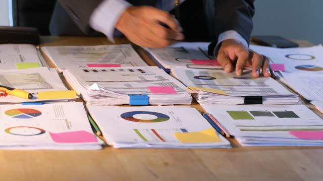 asiatische geschäftsleute verwenden taschenrechner für die analyse von projektunterlagen und grafiken finanzdiagramm, die im hintergrund auf dem bürotisch arbeiten - budget stock-videos und b-roll-filmmaterial