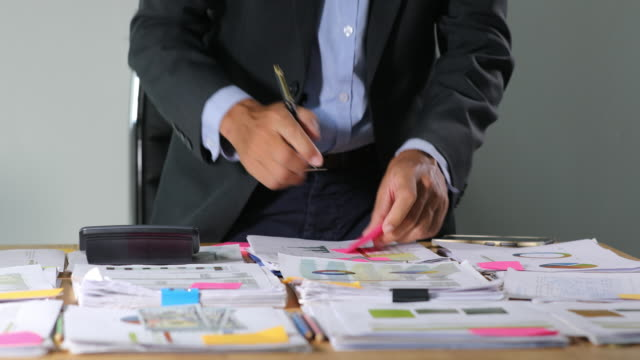 asian businessmen are using calculators for analysis project documents and graph financial diagram working in the background on office table - analysing stock videos & royalty-free footage