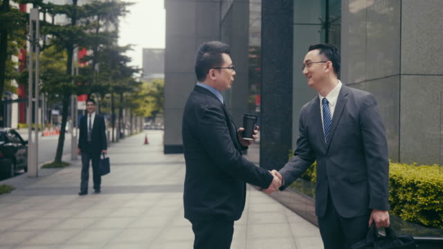 asian businessmen shaking hands in the street corner - asian colleague stock videos & royalty-free footage