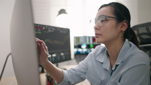 vidéos et rushes de analyse des données des femmes d'affaires asiatiques sur ordinateur dans son bureau - lunettes de vue