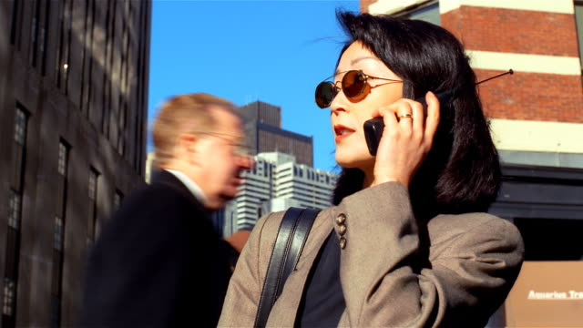asian businesswoman downtown on cellular phone - formato video mpeg video stock e b–roll
