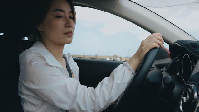 vidéos et rushes de femme d'affaires asiatique conduisant la voiture - assis