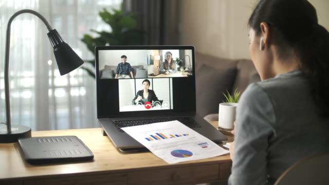 自宅でチームとビデオ通話ミーティングを持つアジアのビジネスウーマン - テレビ会議点の映像素材/bロール