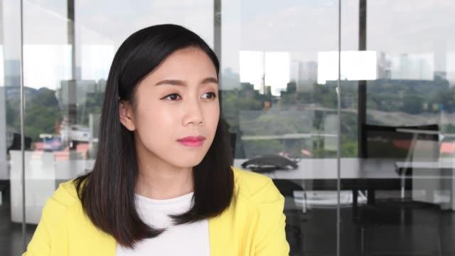 vídeos de stock, filmes e b-roll de mulher de negócios asiático em seu 20s, voltando-se para sorrir para a câmera - gabar se