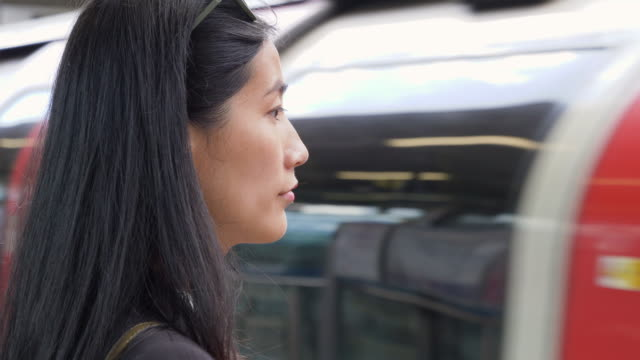 Asian businesswoman is waiting for train arriving in station.