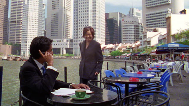 asian businesswoman meeting + shaking hands with businessman on cell phone at outdoor cafe / singapore - pavement cafe stock videos and b-roll footage