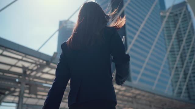 asian businesswoman, office worker walking outside the office. - walkable city stock videos & royalty-free footage