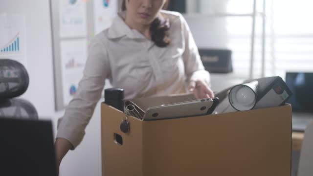 asiatische geschäftsfrau packt sein büro nach der entlassung - carrying stock-videos und b-roll-filmmaterial