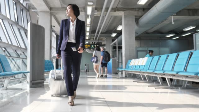 asian businesswoman pulling suitcase at airport, business travel - wheeled luggage stock videos and b-roll footage