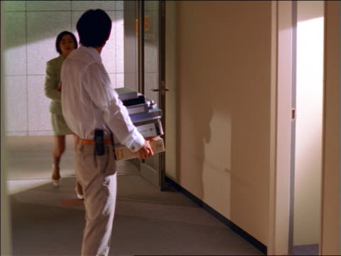 vídeos de stock e filmes b-roll de asian businesswoman puts files on top of pile being carried by man / he drops files answering phone - 1999