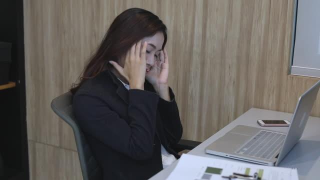 stockvideo's en b-roll-footage met aziatische zakenvrouw serieus aan het werk tot de hoofdpijn, soft focus sea... - werkneemster