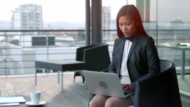 asian businesswoman sitting in the terrace lounge overlooking the city and working on her laptop - minigonna video stock e b–roll