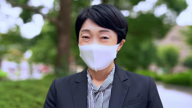 アジアのビジネスウーマンは微笑み、マスクを脱ぐ。コロナウイルスの概念の終わりのためのビデオ。 - absence点の映像素材/bロール