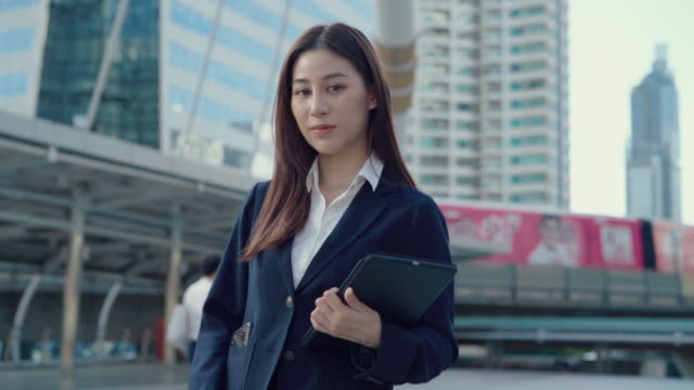 asian businesswoman smiling into the camera while standing in city - part of a series stock videos & royalty-free footage