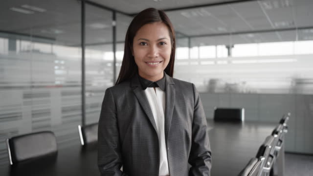 slo mo asian businesswoman smiling into the camera while standing in the conference room - asian and indian ethnicities stock videos & royalty-free footage