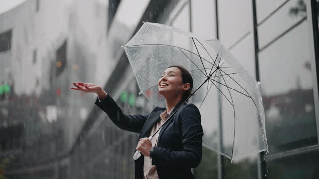 vídeos de stock, filmes e b-roll de empresária asiática em pé com guarda-chuva na chuva - chapéu