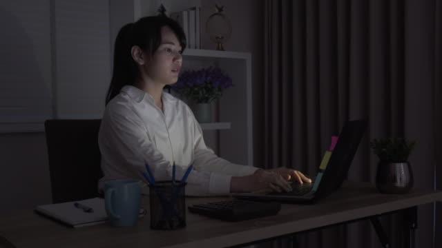 vídeos de stock, filmes e b-roll de trecho asiático da mulher de negócios após o trabalho duro no escritório no conceito escuro, overworked - excesso de trabalho