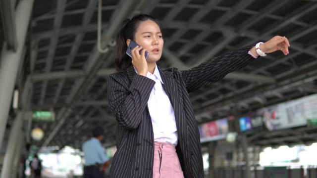 asiatische geschäftsfrau telefonieren während des wartens auf den zug zu kommen. - bahnreisender stock-videos und b-roll-filmmaterial