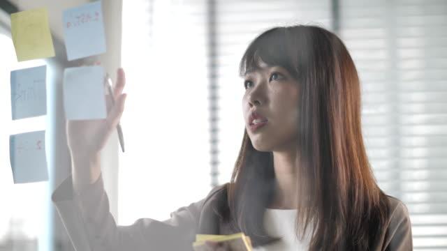 vídeos de stock, filmes e b-roll de mulher de negócios asiática que pensa das idéias e da escrita no borne ele para o projeto seguinte - ideia
